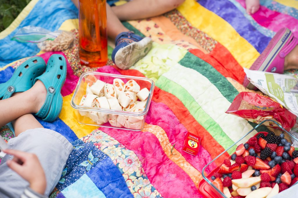 Colourful picnic blanket with children's feet visible and square dish of treats